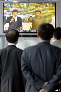 South Koreans watch the two leaders on a television in Seoul
