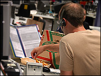 Call centre worker eating pizza and chips at his desk
