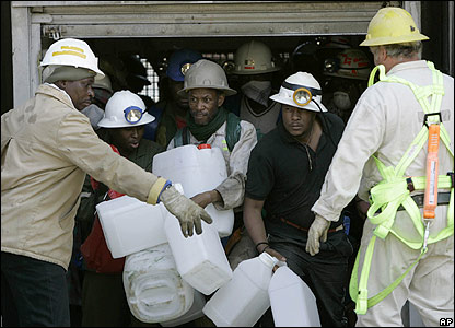Workers bring jerrycans back to the surface