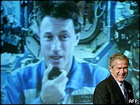 President George W Bush (foreground), with astronaut Michael Foale (onscreen, background). Image: AFP.
