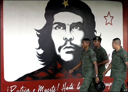 Soldiers in Venezuela walk past a mural of Che Guevara