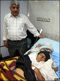 An Iraqi man stands next to his wife at a hospital in Baghdad. She was reportedly injured in a US air raid on the village of al-Jayzani, near Baquba