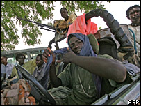 Members of the SLA-Minni Minawi faction drive around a refugee camp in southern Darfur