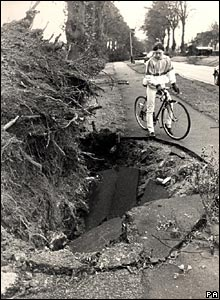 A cyclist views the huge hole left by an uprooted tree on Mote Road, Maidstone, Kent