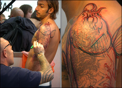 Man having elaborate fish tattooed on shoulder