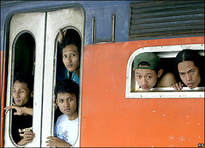 Men board a crowded train at Senen station in Jakarta, Indonesia