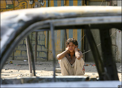 An Iraqi boy looks at a damaged car after a roadside blast in the mostly Shia neighbourhood of Shaab