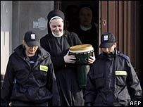 Polish police officers escort a nun from a convent in Kazimierz Dolny
