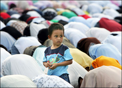 A young boy stands among worshippers as thousands of Filipino Muslims bow in prayer to celebrate Eid