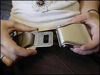 A passenger fastening a seatbelt on an plane