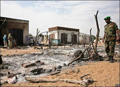 An African Union Mission  military observer surveys the burnt-out marketplace in Muhajariya town in southern Darfur