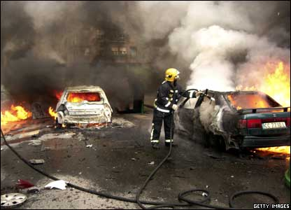 A fireman extinguishes flames at the scene where a car bomb exploded.