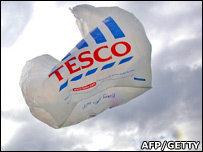 A tesco bag, seen against clouds, blowing in the wind