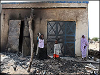 Local people in front of burnt out buildings in Darfur