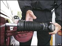 Un hombre pone gasolina en su vehículo.