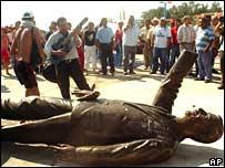 Protesters around the fallen statue of Vicente Fox