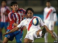 El peruano Juan Vargas (der.) y el paraguayo Dennis Caniza forcejean por la pelota