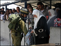 An Israeli officer checks the shopping bag of a Palestinian woman at the Israeli Hawara checkpoint on the outskirts of the northern West Bank city of Nablus (7 August 2007)