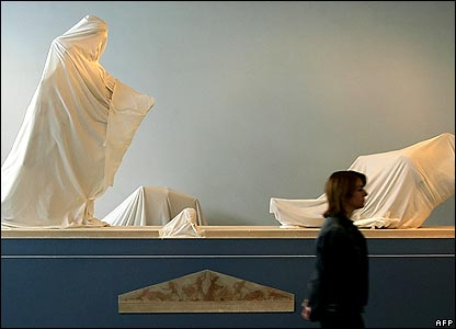 Curator walking past wrapped statues