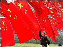 Niño chino, jugando entre banderas