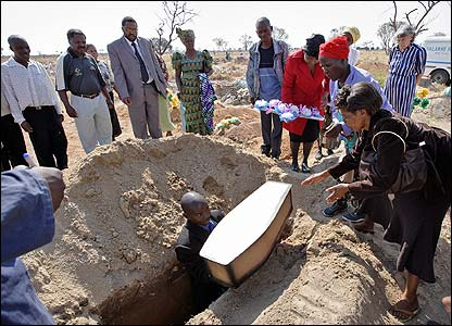 A church pastor lowers the coffin as nine-month-old Vincent is buried among thousands of the city's newly dug child graves