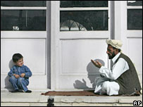 An Afghan boy watches a man offer Eid al-Fitr prayers at Pul-E-Khashti mosque in Kabul, Afghanistan
