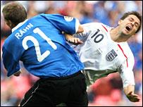 Michael Owen is tackled by Taavi Rahn of Estonia