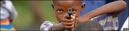 Child plays with a toy gun in a camp for displaced people in DR Congo