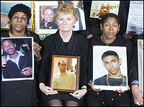 Maureen Miller (centre) with a photo of her son