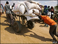 A Somali boy helps push a donkey cart loaded with food aid