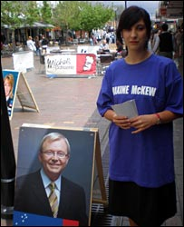 An opposition campaigner, with a picture of Labor leader Kevin Rudd