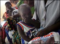 A boy holds a mosquito net at a health clinic in Dar-es Salaam, Tanzania