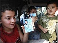 Palestinian children showing Lebanese refugee identity cards