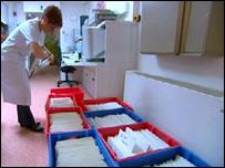 A woman picks up patient files