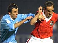 San Marino's midfielder Damiano Vannucci challenges Wales' midfielder David Vaughan