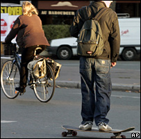 Parisians use a bike and a skateboard to get around the city