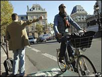 A man hitchhikes while another one rides his bicycle in Paris