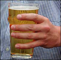 A man holds a pint of beer