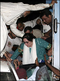 Benazir Bhutto is helped down from her truck into another car (18 October 2007)