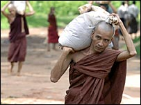 A monk carrying a sandbag in Bago