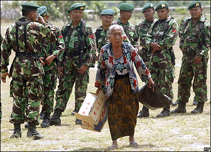 Soldiers look on as an elderly woman gathers up possessions