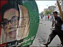 Angry Bhutto supporter carries a piece of wood as he passes a banner of her, Karachi 20 October