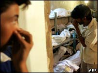 Pakistanis hold their noses as they search for relatives among bodies at the mortuary, Karachi 20 October