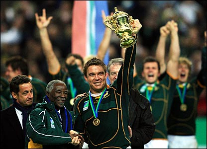 Captain John Smit (right) holds the trophy aloft while shaking hands with South Africa president Thabo Mbeki