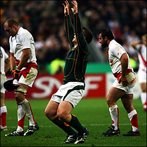 South Africa captain John Smit sinks to his knees and raises his arms in celebration at the final whistle