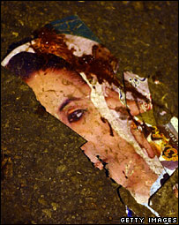 A placard of Benazir Bhutto lies torn after the bomb attacks in Karachi