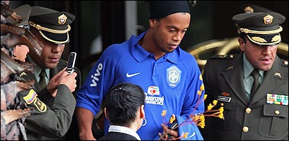 Ronaldinho is escorted out of his hotel in Bogota, Colombia, by police officers