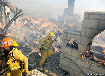 Firefighters work to extinguish the flames at Castle Kashan near Malibu Canyon Road, California