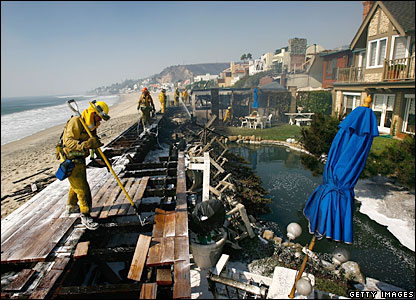 Firefighters mop-up damage at an expensive beach-front home in Malibu