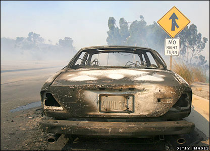 The burned remains of a car on Pacific Coast Highway, Malibu